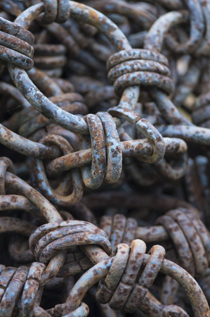 Iron links join iron rings in chaotic mass of rusting chain Фото со стока