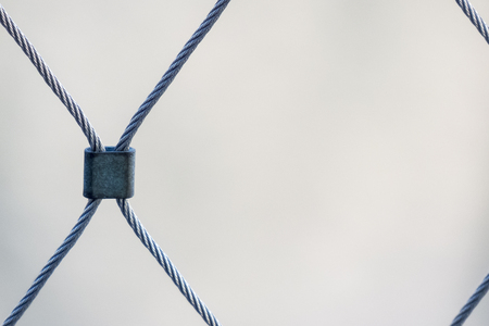 Diamond pattern created by steel clip on wire cable fence Imagens