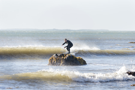 Westport, Massachusetts, USA - July 5, 2014: Surfer off Gooseberry Neck appears to be riding small wave into a rock. Buzzards Bay and Cuttyhunk Island in background.
