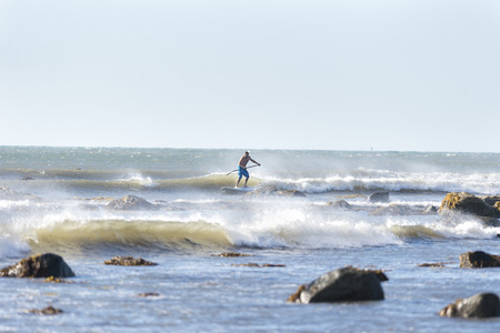 Westport, Massachusetts, USA - July 5, 2014: Stand up paddleboarder off Gooseberry Neck negotiates rocky shoreline in small surf