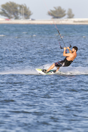 tampa bay: Tampa Bay, Florida, USA - February 28, 2011: Kiteboarder glides across small chop off Fort De Soto Editorial