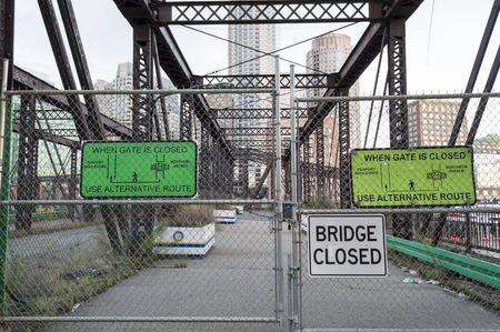 decided: South Boston, Massachusetts, USA - September 15, 2016: Northern Avenue Bridge across Fort Point Channel fenced off and growing more decrepit while its future is being decided