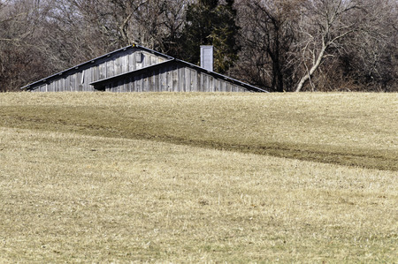 Barn roof peeking over hilly field at Daniel Webster Wildlife Sanctuary Imagens