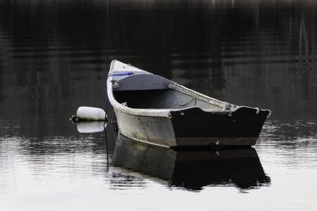 Old skiff bobbing at mooring on calm afternoon Imagens - 69220457