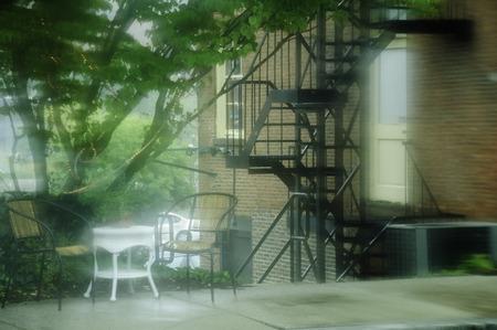 smeary: Rain blurs a summer sidewalk relaxation spot Stock Photo