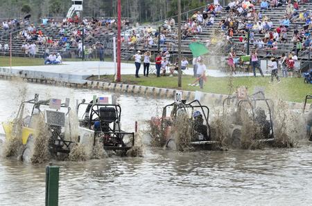 Naples, Florida, Verenigde Staten - 3 maart 2012: Swamp buggies trekken uit de startlijn in haan staarten van modder