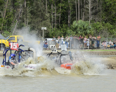 Naples, Florida, USA - March 3, 2012: Swamp buggies pushing bow waves of muddy water