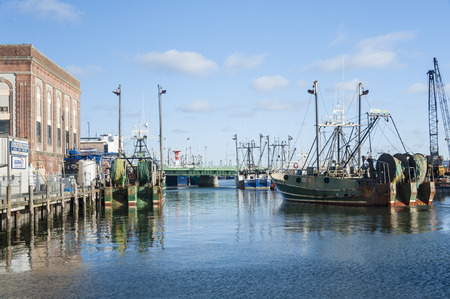 New Bedford, Massachusetts, USA - March 15, 2017: Fishing vessel easing toward dock on New Bedford waterfront