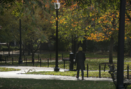 Boston, Massachusetts, USA - November 10, 2007: Woman walking across Boston Common on a chilly autumn day Editorial