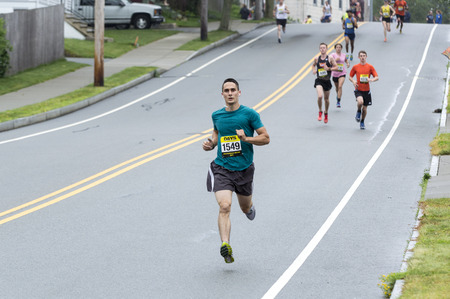 Fairhaven, Massachusetts, USA - June 18, 2017: Runner in the air on downhill section of Fairhaven Road Race