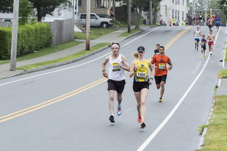 pace: Fairhaven, Massachusetts, USA - June 18, 2017: Runners pick up pace on short downhill section in Fairhaven Road Race Editorial