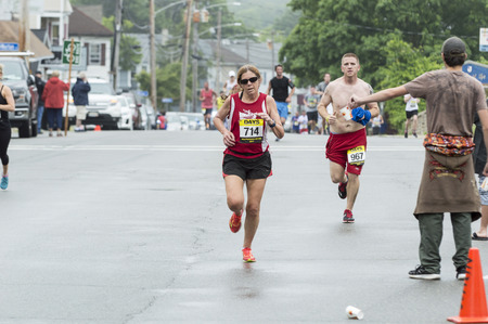Fairhaven, Massachusetts, USA - June 18, 2017: Runners pass water station after push up hill in Fairhaven Road Race