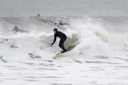 Little Compton, Rhode Island, USA - January 17, 2016: Surfer slides across foamy January wave Redakční