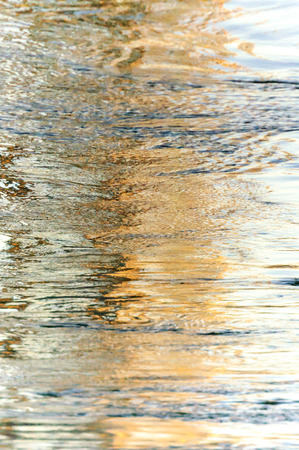 Swirling water breaks up early morning reflections Stock Photo