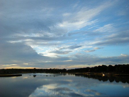 Clouds reflecting off tranquil Mattapoisett River near dawn