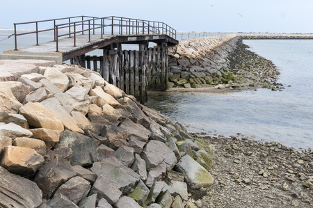 enables: Gap in the breakwater at Plymouth, Massachusetts enables small boats to take a shortcut to leave the harbor when tides are higher