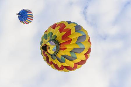 Quechee, Vermont, USA - June 19, 2009: Hot air balloons drifting directly overhead at the Quechee Hot Air Balloon Craft and Music Festival