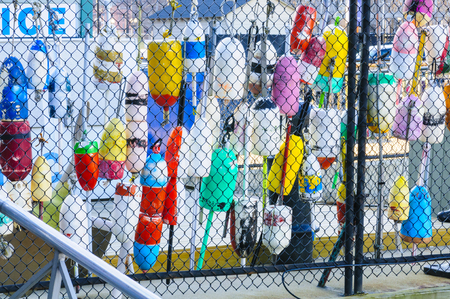 Colorful fishing gear resting against chain link fence Stock Photo