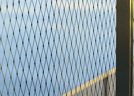 Diamond pattern cable fence with water background Stock Photo