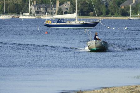 Mattapoisett, Massachusetts, USA - May 29, 2007: Small powerboat skimming toward mouth of Mattapoisett River Редакционное