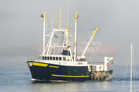 New Bedford, Massachusetts, USA - October 23, 2017: Fishing vessel Monomoy leaving New Bedford harbor on hazy morning with Nantucket Lightship in background Editorial