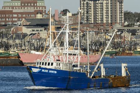New Bedford, Massachusetts, USA - October 31, 2017: Fishing vessel Blue South leaving New Bedford harbor with Nantucket lightship in background
