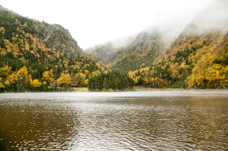 Mountain tops shrouded in mist at Lake Gloriette in New Hampshire