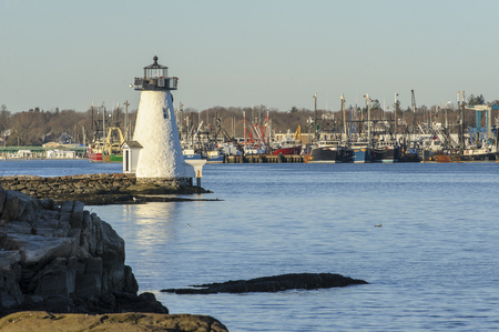 New Bedford, Massachusetts, USA - December 21, 2017:  Palmers Island lighthouse on the Acushnet River with Fairhaven fishing fleet in background Editorial