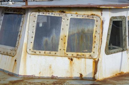Rusting, fogged windows on wheelhouse of old fishing boat