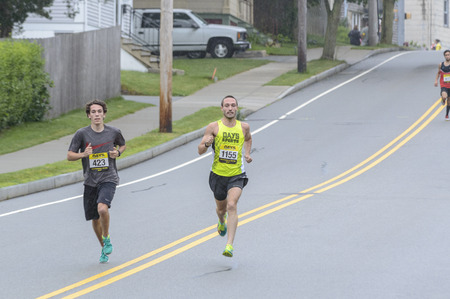 Fairhaven, Massachusetts, USA - June 18, 2017: Runners flying down hill during Fathers Day Road Race