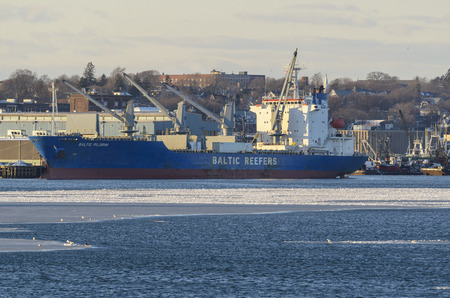 New Bedford, Massachusetts, USA - January 9, 2018: Refrigerated cargo ship Baltic Pilgrim docked in icy New Bedford harbor Editorial