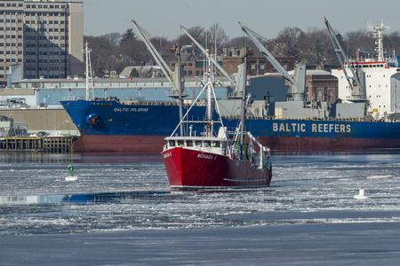 New Bedford, Massachusetts, USA - January 10, 2018: Fishing boat Moragh K leaving icy New Bedford harbor with refrigerated cargo ship in background Redakční