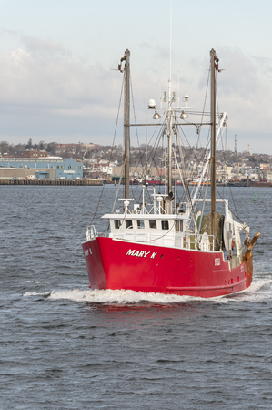 New Bedford, Massachusetts, USA - February 8, 2018: Trawler Mary K leaving port with New Bedford waterfront in background Redakční