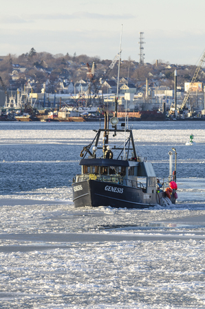 New Bedford, Massachusetts, USA - January 9, 2018: Commercial fishing boat Genesis on icy Acushnet River with New Bedford waterfront in background Editorial