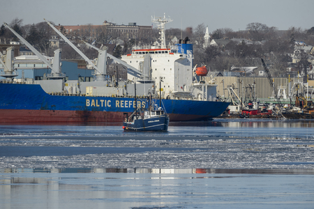 New Bedford, Massachusetts, USA - January 10, 2018: Commercial fishing boat Jessica & Susan with refrigerated cargo ship in background on icy Acushnet River Editorial