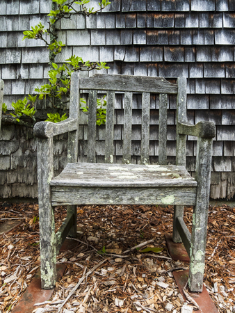 Lopsided wooden chair flecked with lichen in public garden Stock Photo
