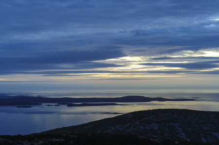 Silhouette of Schoodic Peninsula during cloudy sunrise at Cadillac Mountain