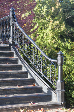 Wrought iron railing on footbridge crossing Willow Lake in Roger Williams Park Stock Photo