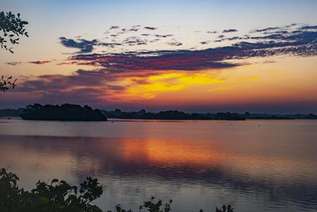 Sunrise illuminating clouds over coastal lagoon at Trustom Pond National WIldlife Refuge 版權商用圖片