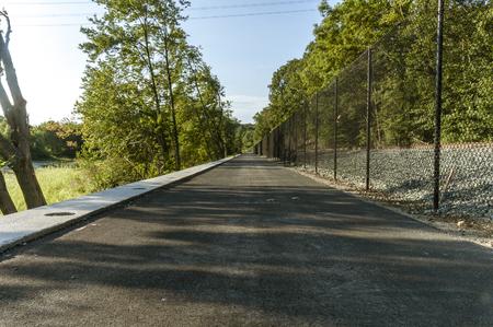 Long bike path straightaway running alongside railroad tracks along Blackstone River