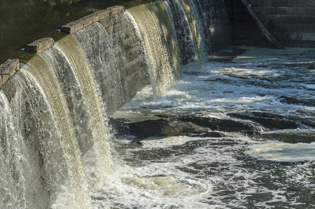 Water spilling over small waterfall on Blackstone River on sunny morning