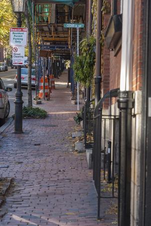 Boston, Massachusetts, USA - November 24, 2007: Tight quarters on Beacon Hill with uneven brick sidewalk and construction scaffolding