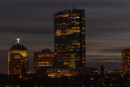 Boston skyline lights up as sunlight fades to night Foto de archivo