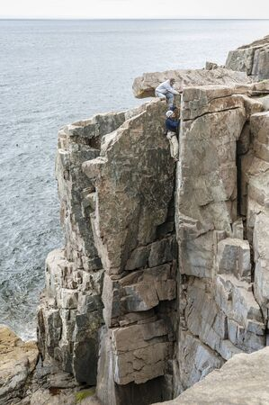 Acadia National Park, Maine, USA - September 11, 2010: Climber nearing top of  Otter Cliff in Acadia National Park