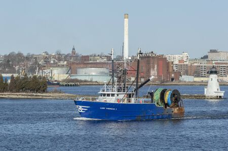 New Bedford, Massachusetts, USA - March 27, 2019: Monkfish trawler Luso American I passing Palmer Island lighthouse on way out of New Bedford Editorial