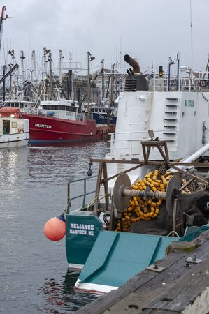 New Bedford, Massachusetts, USA - April 13, 2019: Commercial fishing boat Reliance, hailing port Hampden, Maine, and other vessels docked in New Bedford on rainy morning