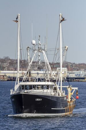 New Bedford, Massachusetts, USA - April 17, 2019: Commercial fishing vessel Liberty leaving New Bedford to go fishing