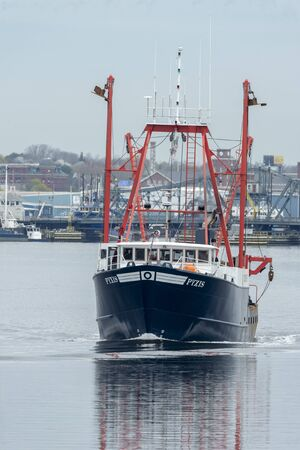 New Bedford, Massachusetts, USA - May 1, 2019: No breeze on Acushnet River as commercial fishing vessel Pyxis heads out on fishing trip