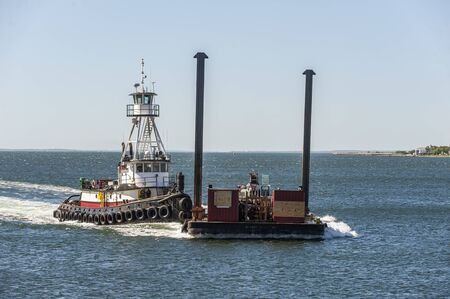 New Bedford, Massachusetts, USA - May 21, 2019: Tug Realist, hailing port New York, New York, pushing barge against stiff wind in outer New Bedford harbor Banco de Imagens - 128022813