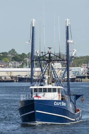 New Bedford, Massachusetts, USA - May 25, 2019: Commercial fishing vessel Capt. Bob, hailing port Cape May, New Jersey, heading to sea with New Bedford waterfront in background Editorial